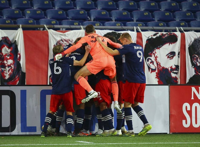 New England Revolution players celebrate  forward Gustavo Bou's winning goal in extra time over the Montreal Impact on Friday at Gillette Stadium.