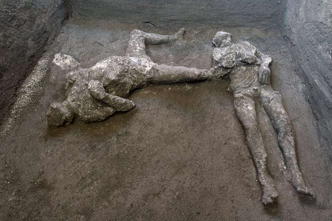 The casts of what are believed to have been a rich man and his male slave fleeing the volcanic eruption of Vesuvius nearly 2,000 years ago are seen in what was an elegant villa on the outskirts of the ancient Roman city of Pompeii destroyed by the eruption in 79 A.D., where they were discovered during recents excavations, Pompeii archaeological park officials said Saturday.