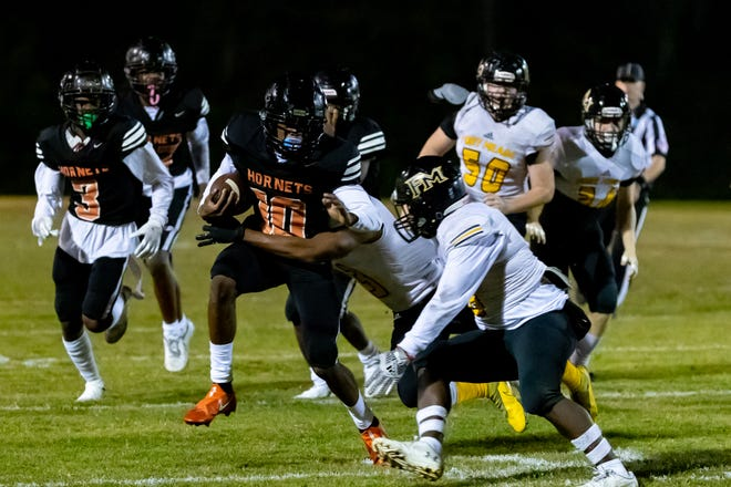 Hawthorne receiver Camren Cohens (10) tries to escape the Fort Meade defense on Friday in Hawthorne.
