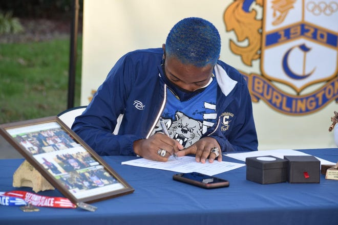 Track and field athlete Kendall Jordan signs her national letter of intent to Kentucky in a curbside ceremony Monday at Cummings High School.