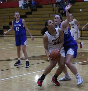 New Philadelphia's Ajia Schreffler drives to the basket past a East Liverpool defender in the season and home opener Friday.