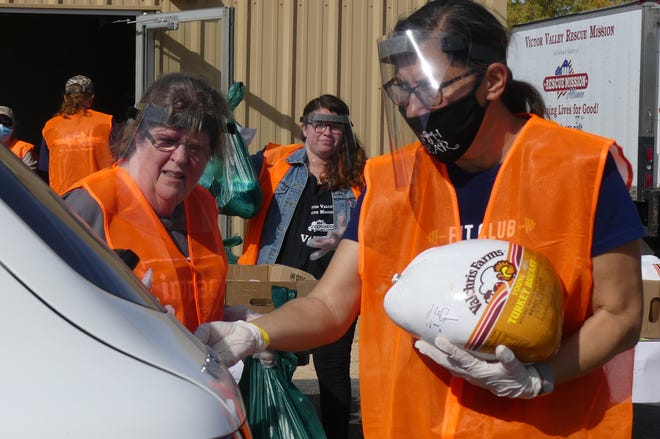 Victor Valley Rescue Mission volunteers load vehicles with free Thanksgiving turkeys and holiday meal items on Saturday, Nov. 21, 2020, during a drive-thru food giveaway at the fairgrounds in Victorville.