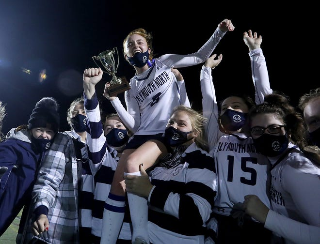 Bella Harvey and Kyleigh Green lift up teammate Emily Jenkins while she holds the Patriot Cup trophy after the Plymouth North field hockey team's 4-0 win over Pembroke in the championship final. [Wicked Local Staff Photo/Robin Chan]