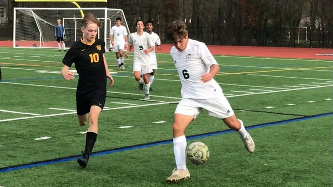 Mainland's Thomas Napoli attempts to control the ball as Moorestown's Cade McGrath defends. The Quakers captured the sectional title with a 2-0 win.