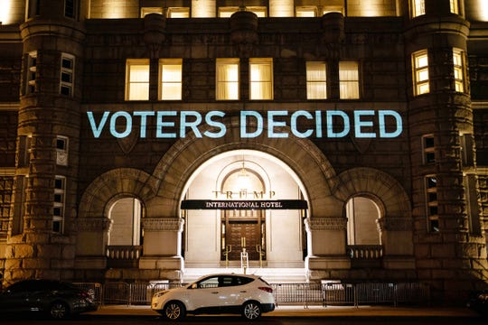 Projections of messages to Republican election officials from Michigan Senate Majority Leader Mike Shirkey and Speaker of the House Lee Chatfield during their visit to the White House light up the front of the Trump Hotel in Washington, D.C.