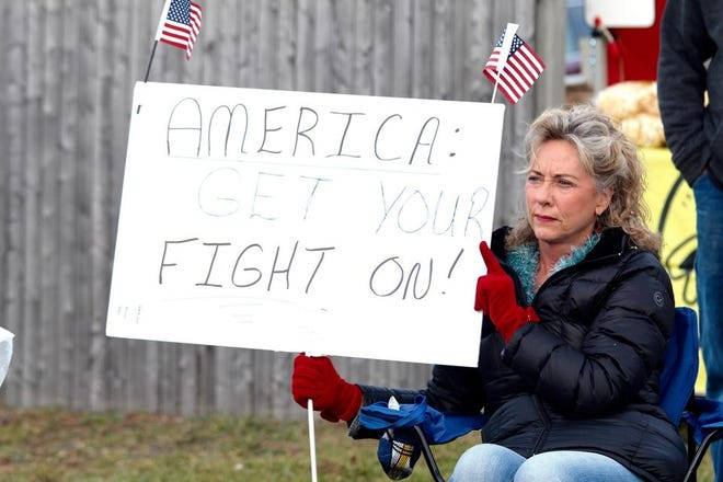 A woman holds a sign at a protest of Michigan's latest pandemic order in Newaygo on Friday, Nov. 20, 2020. Hundreds attended the protest, outside Jimmy's Roadhouse, to decry the order and support restaurants, which are ordered to close dine-in eating for three weeks.