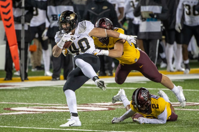 Nov 20, 2020; Minneapolis, Minnesota, USA; Purdue Boilermakers running back Zander Horvath (40) rushes with the ball as Minnesota Golden Gophers linebacker Mariano Sori-Marin (55) makes a tackle in the first half at TCF Bank Stadium. Mandatory Credit: Jesse Johnson-USA TODAY Sports