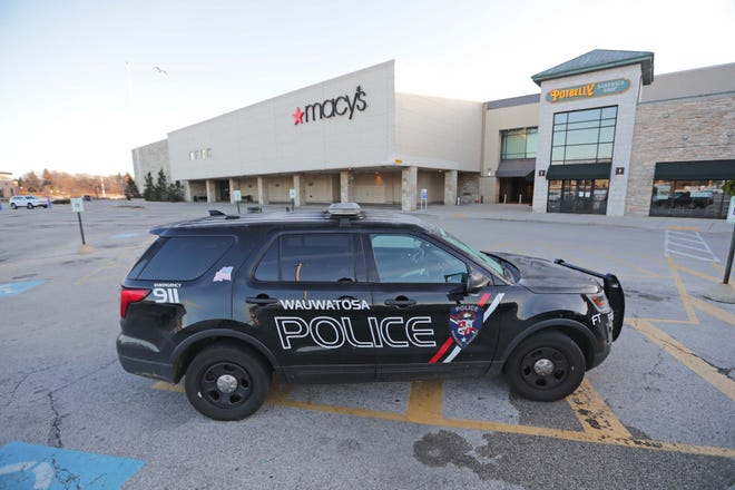 A Wauwatosa police vehicle sits outside Macy's near the entrance to Mayfair mall Saturday, Nov. 21, 2020, in Wauwatosa. A gunman opened fire at Mayfair mall in Wauwatosa Friday afternoon, wounding seven adults and one teenager, officials said.