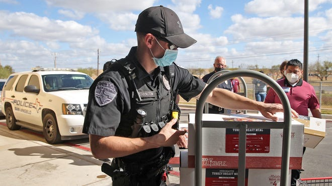 Officers with the San Angelo Police Department gather at the H-E-B store at 5502 Sherwood Way to distribute Thanksgiving Day meals to families in need on Saturday, Nov. 21, 2020.