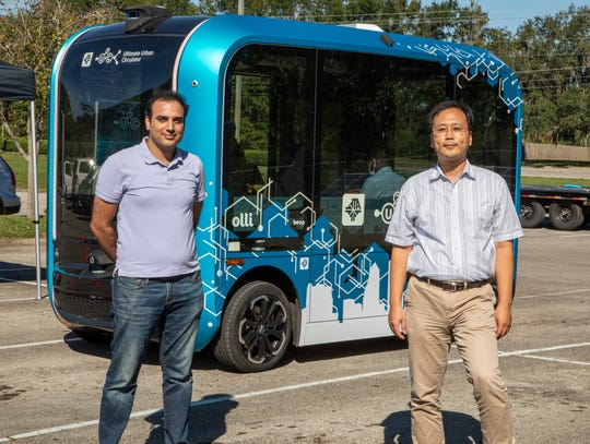 Professors Mohammad Resa Seyedi, left, and Sungmoon Jung with the U2C Autonomous Bus in the parking lot at the FAMU-FSU College of Engineering in Tallahassee, Florida