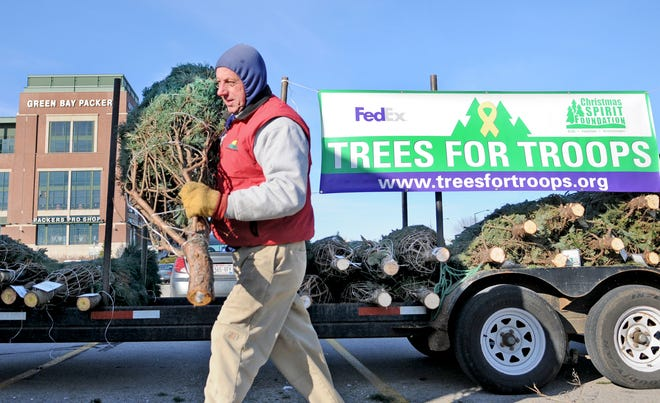 File photo: Jon Bigler of Rolling Hills Tree Farm loads up a truck at the Lambeau Field parking lot with donated Christmas trees for Trees for Troops program. This year 22 member farms of the Wisconsin Christmas Tree Producers Association are aiming to donate 850 trees to members of the armed forces.