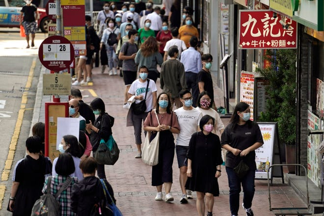 People wearing masks to protect against the coronavirus, walk down a street in Hong Kong. Singapore and Hong Kong have postponed a planned air travel bubble meant to boost tourism for both cities, amid a spike in coronavirus infections in Hong Kong. The air travel bubble, originally slated to begin Sunday, will be delayed by at least two weeks, Hong Kong's minister of commerce and economic development, Edward Yau, said at a news conference on Saturday, Nov. 21, 2020.