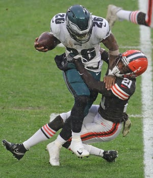 Cleveland Browns' Denzel Ward takes down Philadelphia Eagles' Miles Sanders during a first quarter run on Sunday, Nov. 22, 2020 in Cleveland, Ohio, at FirstEnergy Stadium. [Phil Masturzo/ Beacon Journal]