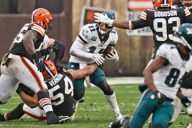 Philadelphia Eagles quarterback Carson Wentz (11) is sacked by Cleveland Browns defensive end Olivier Vernon (54) during the second half of an NFL football game, Sunday, Nov. 22, 2020, in Cleveland. (AP Photo/Ron Schwane)