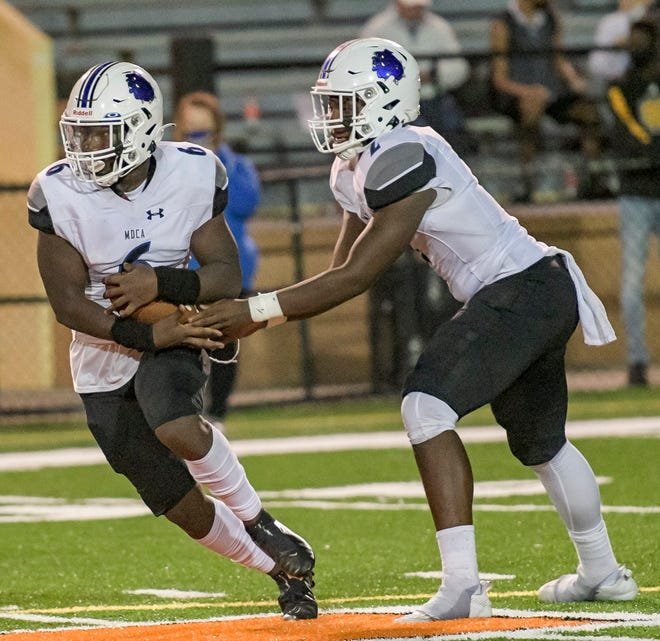 Mount Dora Christian Academy quarterback Ty'quan Wiggins (2) hands off to Terris Wilson (6) during Saturday's Sunshine State Athletic Conference championship game against Orlando Christian Prep at Bryant Stadium in Lakeland. [PAUL RYAN / CORRESPONDENT]