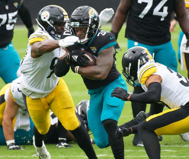 Jaguars running back James Robinson (30) is hit by Pittsburgh Steelers inside linebacker Vince Williams (98) and free safety Minkah Fitzpatrick (39) during a Nov. 22 game.