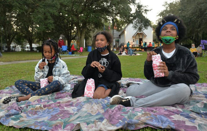 Friends Amerie Johnson, 7, Naiomi Sims, 9, and Janae Brown, 12, get settled in as they prepare to watch the movie.
