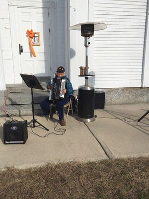 Jane French plays her accordion by the heater during the Congregational Church of Phillipston Thanksgiving Sunday service held outdoors on the town common.