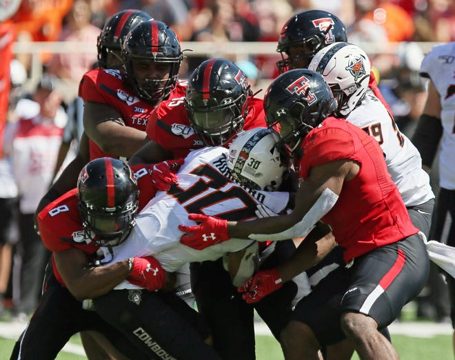 Texas Tech defenders gang tackle Oklahoma State running back  Chuba Hubbard (30) during the Red Raiders' 45-35 victory last year at Jones AT&T Stadium. The two teams meet again at 11 a.m. Saturday at Boone Pickens Stadium in Stillwater, Oklahoma. [Sam Grenadier/A-J Media]