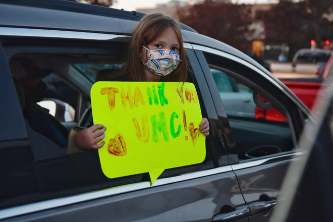 Lillie Stone holds a handmade sign as she prepared for Saturday evening's Park and Pray event at University Medical Center.