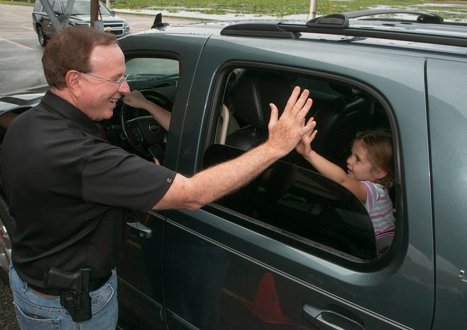 Polk County Sheriff Grady Judd high-fives Harper Kiper, 5, as her family drives through the PCSO's turkey giveaway at the Lakes Church in Lakeland.
