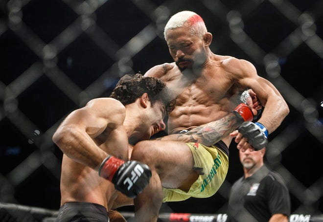 Deiveson Figueiredo, right, knees Alexandre Pantoja during a July 2019 mixed martial arts bout at UFC 240 in Edmonton, Alberta. Figueiredo stopped Alex Perez with a guillotine choke in the first round at UFC 255 on Saturday night, defending his men's 125-pound belt for the first time with another impressive stoppage.
