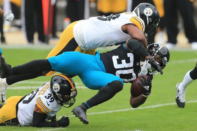 Jacksonville Jaguars running back James Robinson (30) is brought down by Pittsburgh Steelers linebacker Vince Williams, top, and safety Minkah Fitzpatrick (39) during the first half Sunday in Jacksonville.