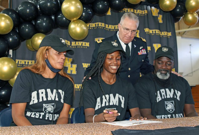 Trinity Hardy, center, signs with West Point as her parents, Felicia Hardy, left, and Roger Hardy, right and Major Charles Cook look on during a signing ceremony on Saturday afternoon at the Jack Deedrick Gymnasium in Winter Haven.