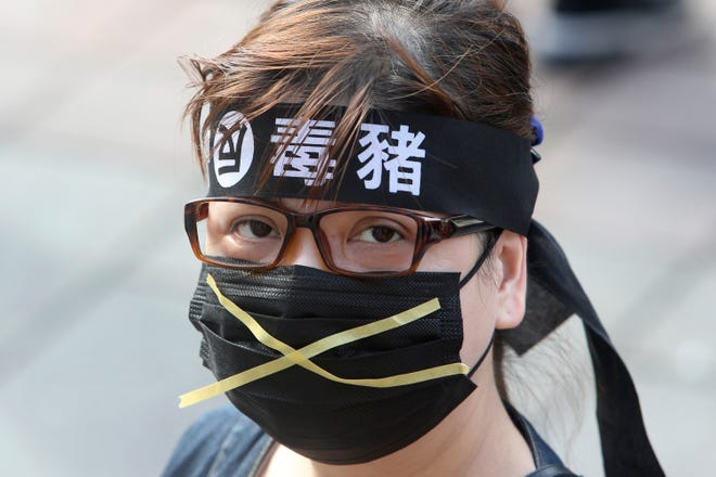 """A Taiwanese woman wears a headband with a slogan """"Anti-poisoned pork"""" during a protest in Taipei, Taiwan, on Sunday. Thousands of people marched in streets on Sunday demanding the reversal of a decision to allow U.S. pork imports into Taiwan, alleging food safety issues."""
