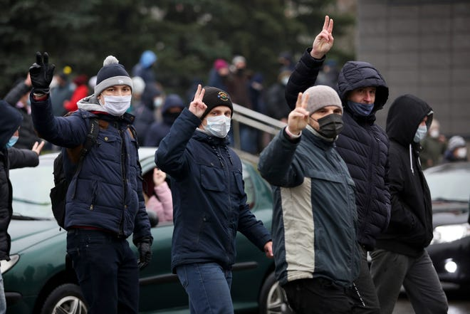Demonstrators wearing face masks to help curb the spread of the coronavirus gesture during an opposition rally to protest the official presidential election results in Minsk, Belarus, on Sunday. The Belarusian human rights group Viasna says more than 140 people have been arrested and many of them beaten by police during protests calling for the country's authoritarian president to resign. The demonstrations that attracted thousands were the 16th consecutive Sunday of large protests against President Alexander Lukashenko.