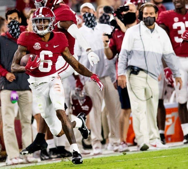 Alabama wide receiver DeVonta Smith (6) heads for a long gain as coach Nick Saban watches during the team's game against Kentucky on Saturday in Tuscaloosa, Ala.