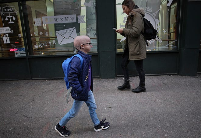 In this Feb. 12, 2019 photo, Meghan Waldron walks down the street in Boston. Waldron is a student at Emerson College with progeria, one of the world's rarest diseases. The first treatment has been approved for progeria, Friday, Nov. 20, 2020.  The U.S. Food and Drug Administration on Friday approved Zokinvy which was shown in testing to extend patients' lives by 2 ½ years on average.