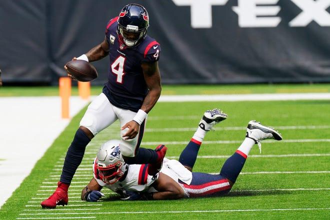 Houston Texans quarterback Deshaun Watson runs past New England Patriots linebacker Josh Uche during the first half of an NFL football game Sunday in Houston.