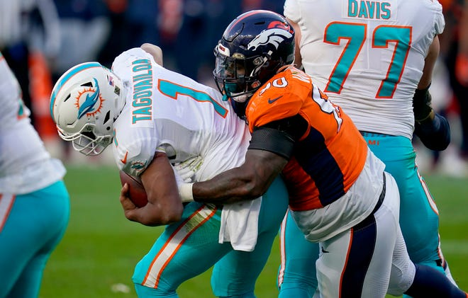 Denver Broncos defensive end DeShawn Williams (90) sacks Miami Dolphins quarterback Tua Tagovailoa (1) during the second half of an NFL football game, Sunday, Nov. 22, 2020, in Denver.
