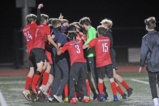 The Narragansett boys soccer team celebrates its 3-0 win over Johnston in the Division III championship game on Saturday night. [The Providence Journal / Eric Rueb]