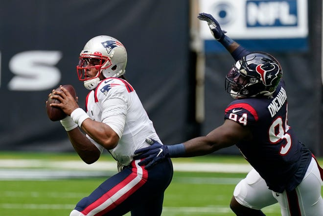 Patriots quarterback Cam Newton (1) is pressured by Houston Texans defensive end Charles Omenihu (94) during the second half of Sunday's game in Houston.