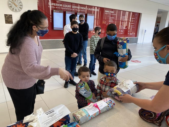 Tina Tiffany, 63, helps her grandsons two-year-old Linkon Edwards, 2; Marquis Edwards, 4, and Nathan Edwards, 10, select blankets in the San Joaquin Superior Courthouse lobby Saturday morning after  adopting the brothers during the 21st annual National Adoption Day event.