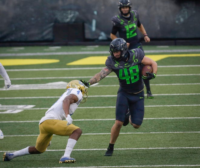 Oregon tight end Hunter Kampmoyer (48) pushes away UCLA defensive back Stephan Blaylock for a big pass completion from Tyler Shough (12) during the fourth quarter of Saturday's game.