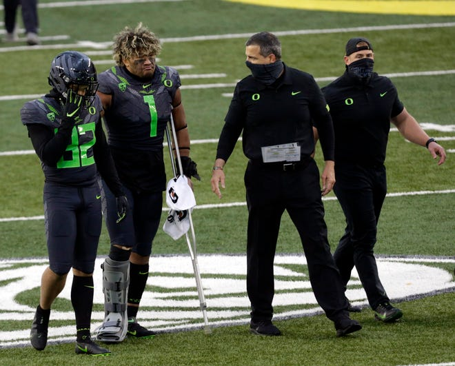 Oregon coach Mario Cristobal talks with linebacker Noah Sewell (1) as he leaves the field with safety Jordan Happle (32) after the Ducks' 38-35 win against UCLA on Saturday at Autzen Stadium.