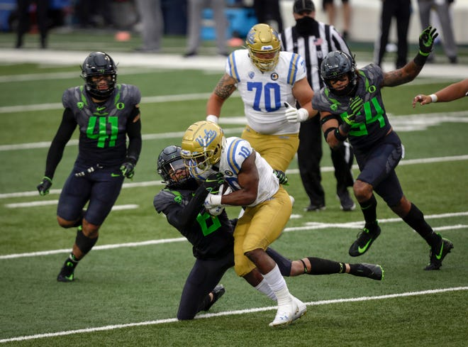 Oregon safety Nick Pickett (6) hauls down UCLA running back Demetric Felton (10) as Oregon linebackers Isaac Slade-Matautia (41) and Dru Mathis (54) come in on the play during the third quarter last Saturday.