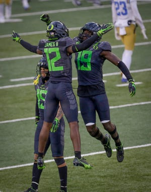 Oregon Ducks cornerback DJ James (12) and Oregon Ducks safety Jamal Hill (19) celebrate after the Oregon defense stopped UCLA on fourth down to seal the Ducks 38-35 win during their Pac12 Conference game at Autzen Stadium in Eugene, Oregon on November, 21, 2020.