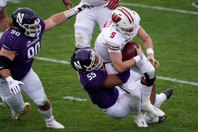 Wisconsin quarterback Graham Mertz is sacked by Northwestern defensive end Eku Leota during the first half Saturday in Evanston.