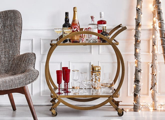 CHEERS! Tiny white Christmas lights wrapped around birch branches add a festive feel to this holiday drink cart. (Photo by Antonis Achilleos)