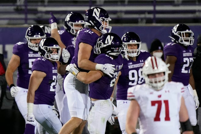 Northwestern players celebrate after they defeated Wisconsin 17-7 in an NCAA college football game in Evanston, Ill., Saturday, Nov. 21, 2020.
