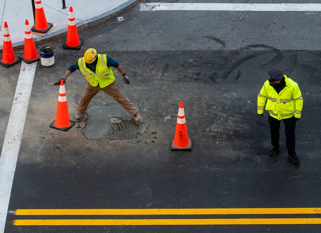 WORCESTER - Worcester Police Officer Jay Bishop watches traffic while construction worker Joe Estremera places cones around fresh concrete as the redesign of Main Street continues Friday.