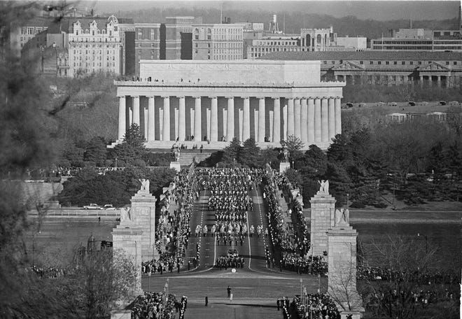The funeral procession for President John Fitzgerald Kennedy, the nation's youngest president struck down by an assassin's bullets, crossed the bridge leading to Arlington National Cemetery in Arlington, Va., Nov. 25, 1963. The procession slowly moves over the Memorial Bridge, with the Lincoln Memorial in the background, a monument to another slain president.