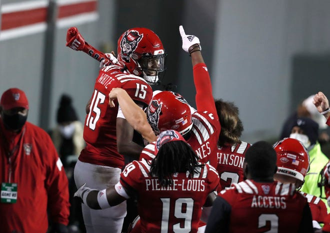 N.C. State cornerback Aydan White (15) celebrates with the turnover bone after intercepting the ball during the second half of N.C. State's 15-14 victory over Liberty at Carter-Finley Stadium in Raleigh, N.C., Saturday, Nov. 21, 2020.