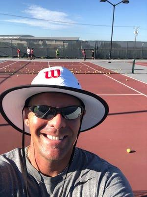 Coach Wyatt Johnson on the outdoor tennis courts.