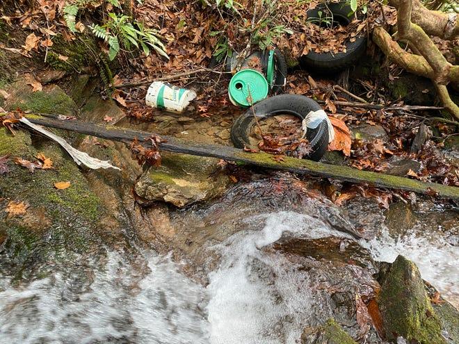 Trash is seen strewn near Tucker Creek Falls off N.C. 215 in Pisgah National Forest.