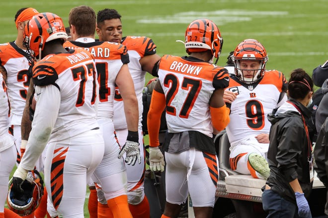 Nov 22, 2020; Landover, Maryland, USA; Cincinnati Bengals quarterback Joe Burrow (9) shakes hands with teammates prior to being carted off the field after injuring his left knee against the Washington Football Team in the third quarter at FedExField.
